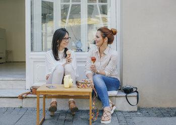 Two friends enjoying ice cream in the city - MOMF00179