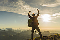 Austria, Salzkammergut, Hiker reaching summit, raising arms, cheering - UUF11002