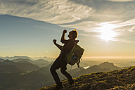 Austria, Salzkammergut, Hiker reaching summit, raising arms, cheering - UUF11005