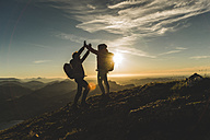 Austria, Salzkammergut, Cheering couple reaching mountain summit - UUF11023