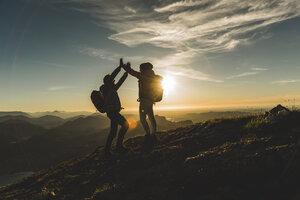 Austria, Salzkammergut, Cheering couple reaching mountain summit - UUF11023