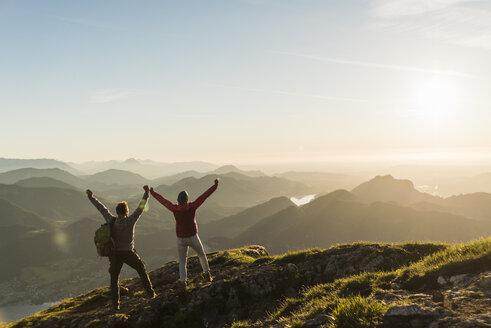 Austria, Salzkammergut, Cheering couple reaching mountain summit - UUF11026