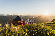 Hiker lying in grass, taking a break and listening music with headphones - UUF11041