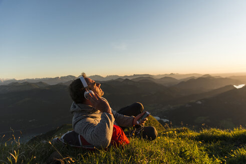 Hiker lying in grass, taking a break and listening music with headphones - UUF11044