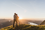 Austria, Salzkammergut, Couple standing on mountain summit, enjoying the view - UUF11047
