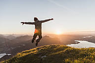 Austria, Salzkammergut, Hiker on mountains summit jumping for joy - UUF11050