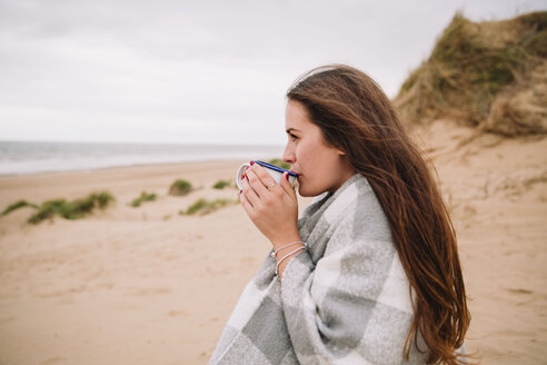 Young woman with cup of hot chocolate on the beach - NMSF00128