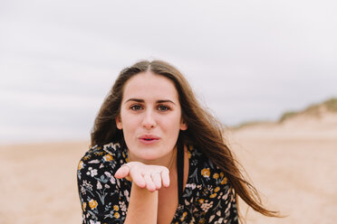Portrait of young woman blowing kiss on the beach - NMSF00134