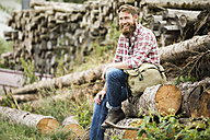 Laughing bearded man sitting on stack of wood - MAEF12378