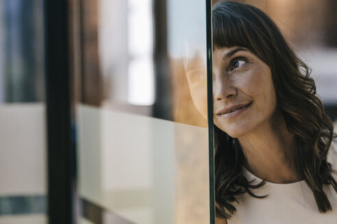 Portrait of a businesswoman looking through glass pane - KNSF01988