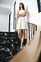 Successful businesswoman standing on staircase - KNSF02003