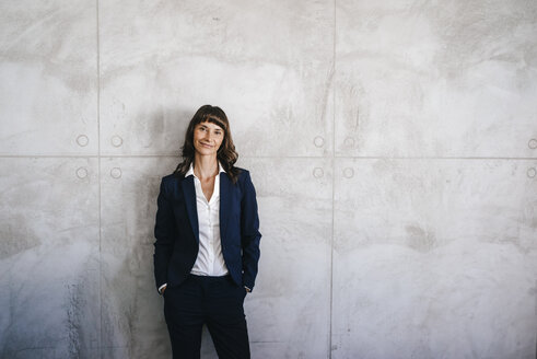 Businesswoman leaning against office wall with hands in pockets - KNSF02006