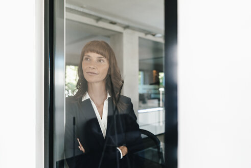 Confident businesswoman looking out of window - KNSF02012