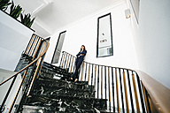 Successful businesswoman standing on staircase - KNSF02015