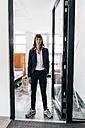 Businesswoman wearing trainers, standing in open door - KNSF02021