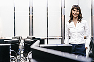 Successful businesswoman standing in office, looking at camera - KNSF02042