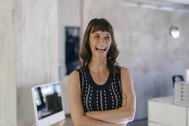 Businesswoman standing in office with arms crossed - KNSF02060