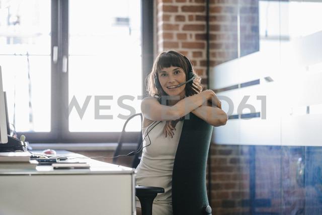 Woman sitting in office, wearing headset - KNSF02081