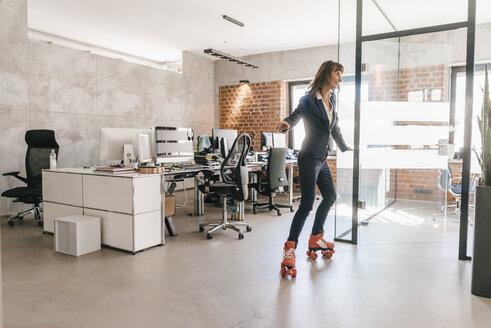 Successful businesswoman wearing roller skates in office - KNSF02090