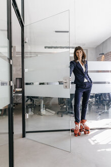 Businesswoman wearing rollerblades, opening glass door - KNSF02093