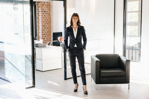 Successful businesswoman standing in office with hands in pockets - KNSF02105