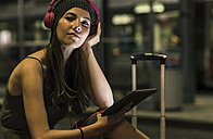 Portrait of young woman with headphones and tablet waiting at station by night - UUF11053