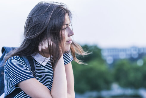Pensive young woman with backpack leaning on railing - UUF11056