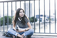 Portrait of young woman with cell phone sitting on a bridge - UUF11059