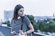 Portrait of young woman with backpack and cell phone - UUF11062