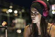 Portrait of young woman with headphones at night - UUF11068