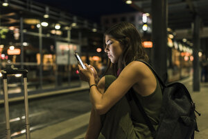 Young woman with backpack and baggage waiting at the station by night using cell phone - UUF11071