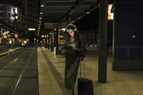 Young woman with headphones and tablet waiting at station by night - UUF11074