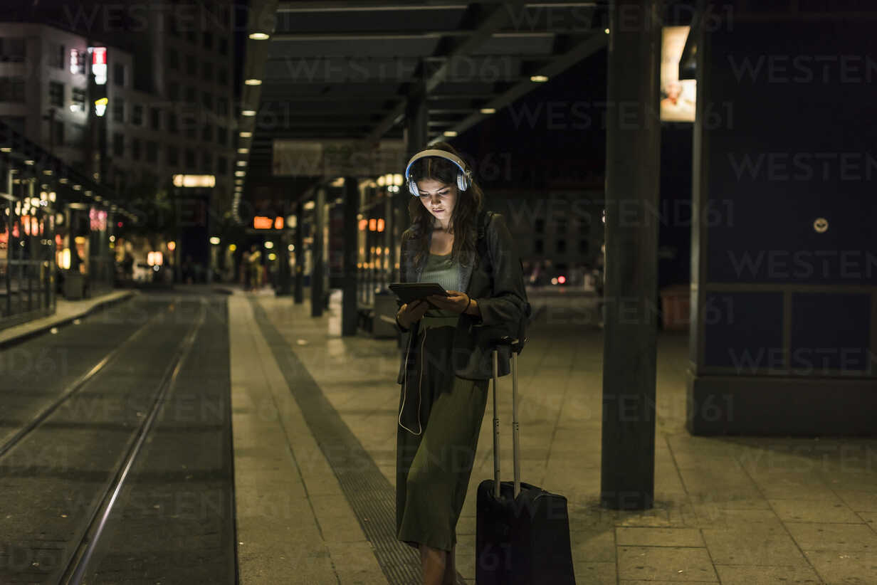 Young woman with headphones and tablet waiting at station by night - UUF11074 - Uwe Umstätter/Westend61