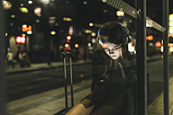 Young woman with headphones waiting at the station by night using tablet - UUF11077