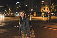 Portrait of young businesswoman with baggage and cell phone at night - UUF11080