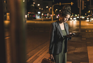 Young businesswoman with leather bag looking at cell phone by night - UUF11083