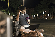Young woman with smoothie sitting on bench at night using laptop - UUF11086