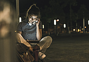 Young woman with smoothie sitting on bench at night using tablet and headphones - UUF11089