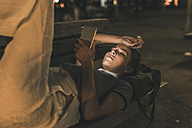 Young woman lying on bench at night using cell phone - UUF11092