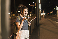 Portrait of young woman on the phone waiting at station by night - UUF11095
