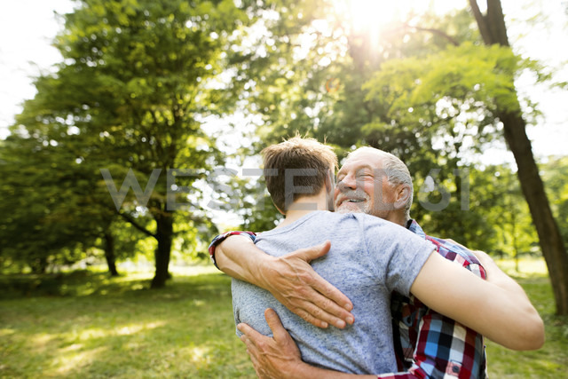 Happy senior father hugging his adult son in a park - HAPF01861 - HalfPoint/Westend61