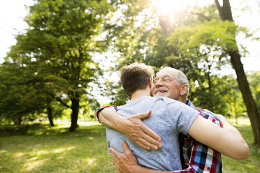 Happy senior father hugging his adult son in a park - HAPF01861