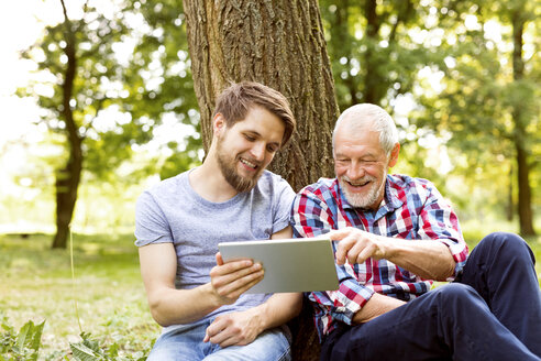 Happy senior father sitting besides his adult son in a park looking at tablet - HAPF01864