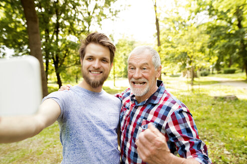 Portrait of senior father and his adult son taking selfie in a park - HAPF01867