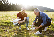 Senior father and his adult son with drone on a meadow - HAPF01870