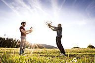 Senior father and his adult son with drone on a meadow - HAPF01873