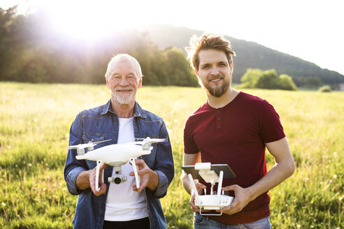Portrait of senior father and his adult son with drone on a meadow - HAPF01876