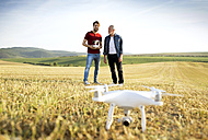 Senior father and his adult son with drone on a field - HAPF01879
