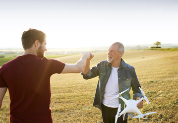 Senior father and his adult son with drone on a field - HAPF01882