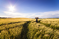 Back view of woman standing in grain field at sunset - SMAF00759